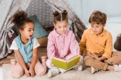 cute little children sitting on carpet and reading book together