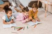 high angle view of adorable multiethnic children lying on carpet and studying together