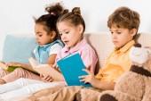 krásné mnohonárodnostní děti sedí na pohovce a společné čtení knihy