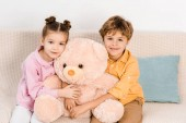 Fotografie adorable happy kids hugging pink teddy bear and smiling at camera