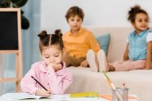 adorable little child writing with pencil while friends sitting behind
