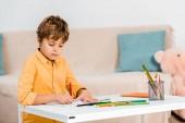 koncentrált fiú tollal írás, és tanulmányozza a táblázat otthon