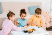 adorable little multiethnic children painting together