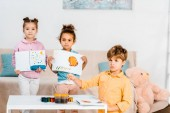 adorable multiethnic children holding pictures and looking at camera while painting together