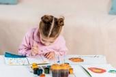imádnivaló koncentrált gyermek ül, és a kép festése