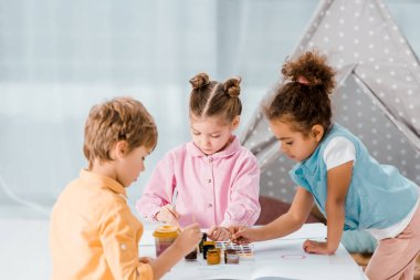 cute multiethnic children sitting and drawing together