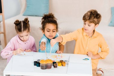 high angle view of cute multiethnic children sitting and drawing together