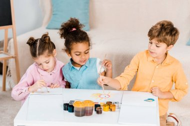 beautiful multiethnic children drawing with paint brushes together
