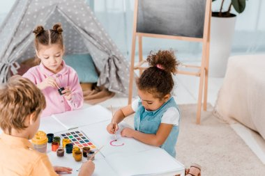 high angle view of adorable little multiethnic kids drawing together
