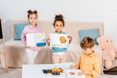 cute multiethnic kids holding pictures and looking at camera while painting together