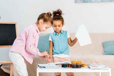 adorable focused multiethnic children painting together