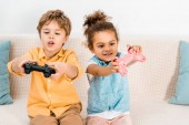 Cute emotional multiethnic kids sitting on couch and playing video game with joysticks