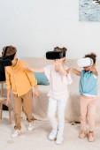 Fotografia adorabili bambini multietnici che giocano insieme nella cuffie di realtà virtuale