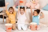 roztomilý šťastné děti sedí na koberci a drží boxy s popcorn
