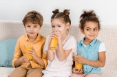 adorable multiethnic children sitting together and drinking juice