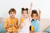adorable multiethnic children holding glasses of juice and showing thumbs up