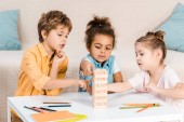 Fotografie cute focused children building tower from wooden blocks on table