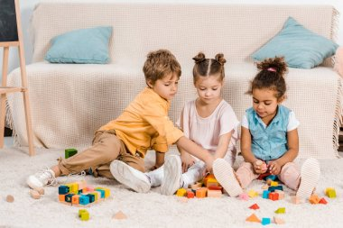 Adorable little ethnic children playing with colorful cubes on carpet stock vector