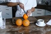 Oříznout obrázek dívky Smíšené rasy, v bílém rouchu řezání pomeranče ráno v kuchyni