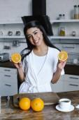 usmívající se dívka krásná Smíšené rasy v bílé roucho hospodářství řežte oranžové a hledáte fotoaparát ráno v kuchyni