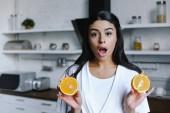 Fotografia ragazza della corsa mixed scioccato in veste bianca holding taglio arancione e che guarda alla macchina fotografica mattina in cucina