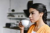 Fotografia Ritratto di ragazza bella corsa mixed in camicia arancione bere caffè mattina in cucina