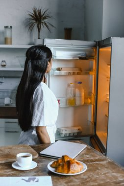 back view of mixed race girl in white robe looking into fridge in morning in kitchen