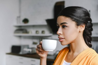 portrait of beautiful mixed race girl in orange shirt drinking coffee in morning in kitchen