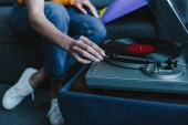 Photo cropped image of mixed race girl turning on gramophone with retro vinyl at home