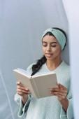 Fotografia ragazza bella corsa mixed in maglione turchese e libro di lettura archetto a casa