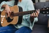 oříznutý obraz dívky Smíšené rasy, tyrkysový svetr hrál na akustickou kytaru na pohovce doma