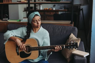 beautiful mixed race girl in turquoise sweater and headband playing acoustic guitar on sofa at home