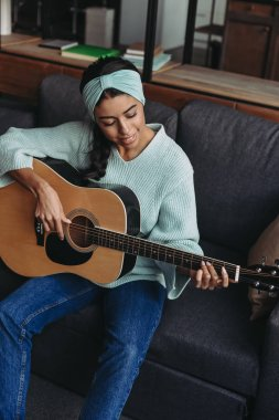 high angle view of beautiful mixed race girl in turquoise sweater and headband playing acoustic guitar on sofa at home