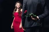 Selektivní fokus ukryl růže za zády s ženou v červených šatech na izolované na černém pozadí