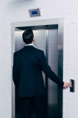 back view of man in black suit pressing elevator button