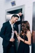 Fényképek pár formális viselni holding pezsgőspoharak, beszél, és várakozás-re lift