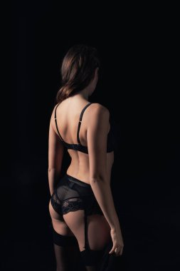 back view of woman in lingerie isolated on black