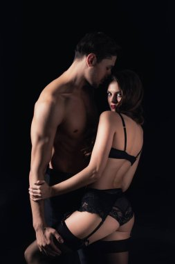 woman in lingerie looking at camera and posing with shirtless man isolated on black