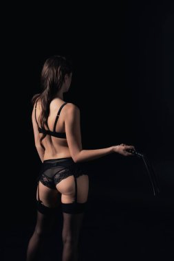 back view of woman holding leather flogging whip isolated on black