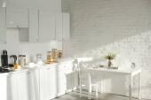 sluneční světlo v bílé moderní kuchyně s kuchyňským nádobím