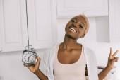 Fotografie Veselá africká americká žena držící hodiny a znamení míru zobrazení