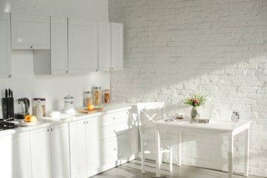 sunlight in white modern kitchen with cooking utensils
