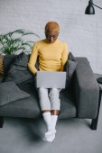focused african american woman with short hair sitting on sofa and using laptop