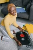 africká americká žena s krátkými vlasy drží vinylová deska poblíž gramofon