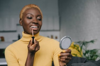 cheerful african american woman applying lip gloss and looking in mirror
