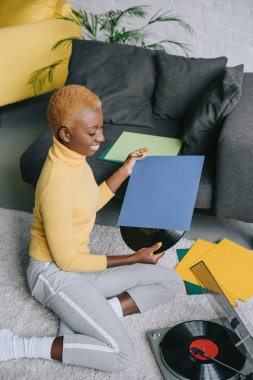 attractive african american woman holding vinyl record and sitting on carpet