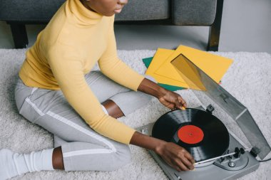 cropped view of african american woman using record player on carpet