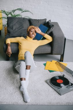 african american woman with short hair sitting on carpet near record player