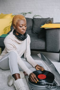 dreamy african american woman sitting on carpet in headphones near record player