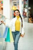 gyönyörű lány gazdaság bevásárló táskák és látszó-on fényképezőgép Mall